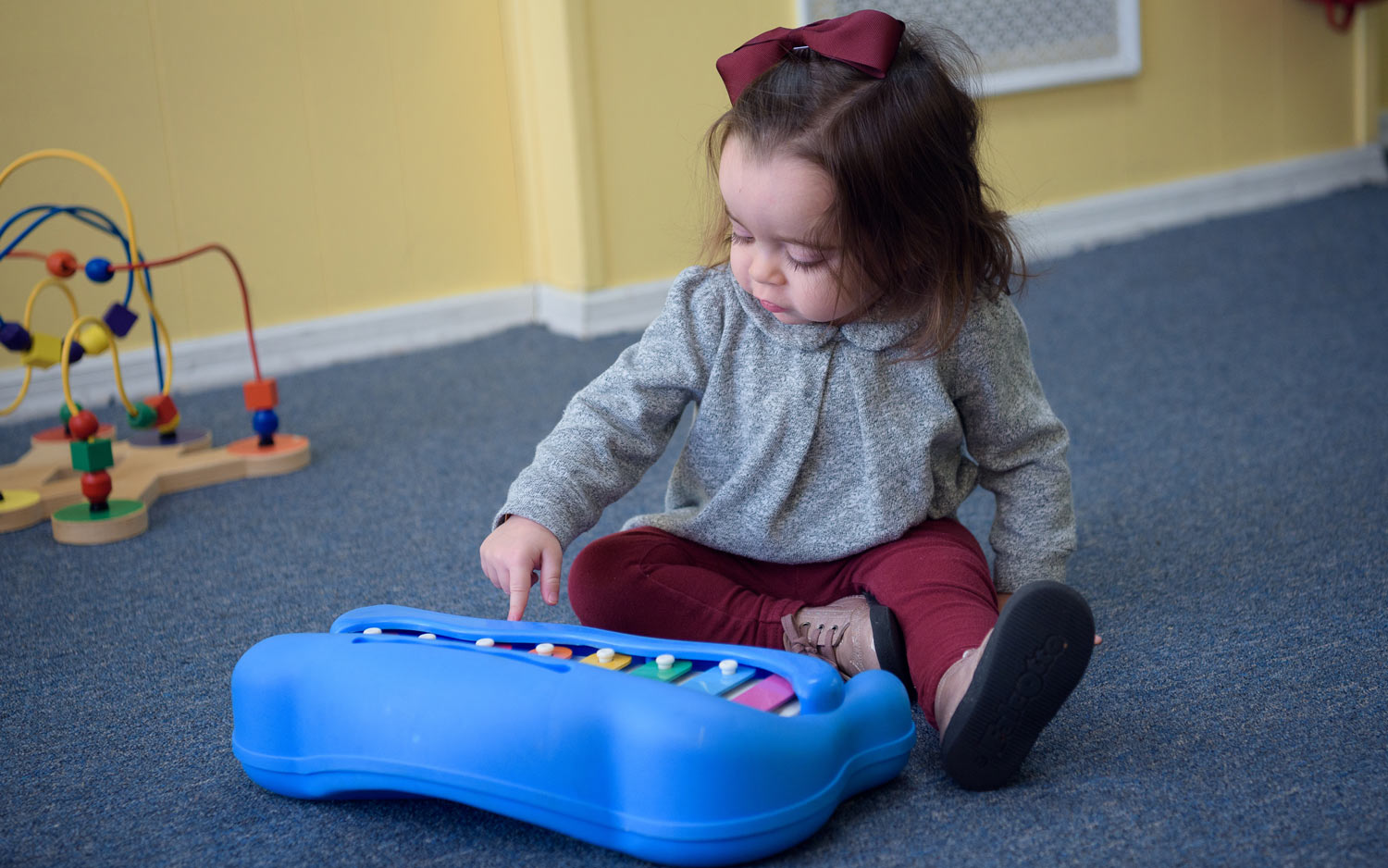 Girl from the Mommy and Me Division playing with a xylophone