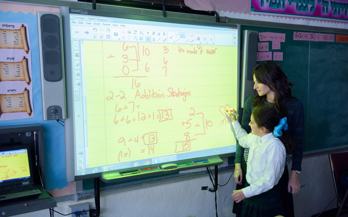 Girls Elementary Division teacher teaching math to a student