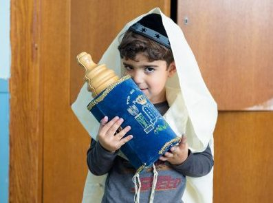 Boy from the Preschool Division wearing a Talis and kissing a Torah