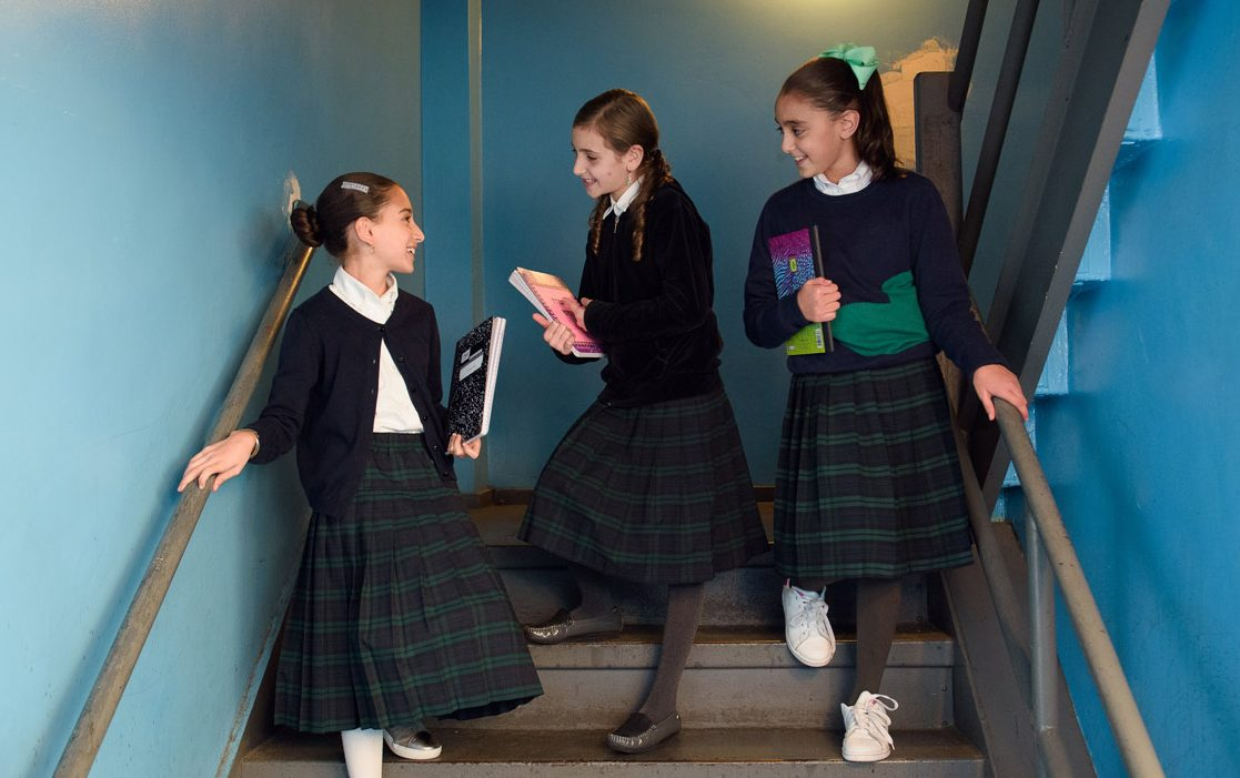 Girls Elementary Division students talking on the stairs