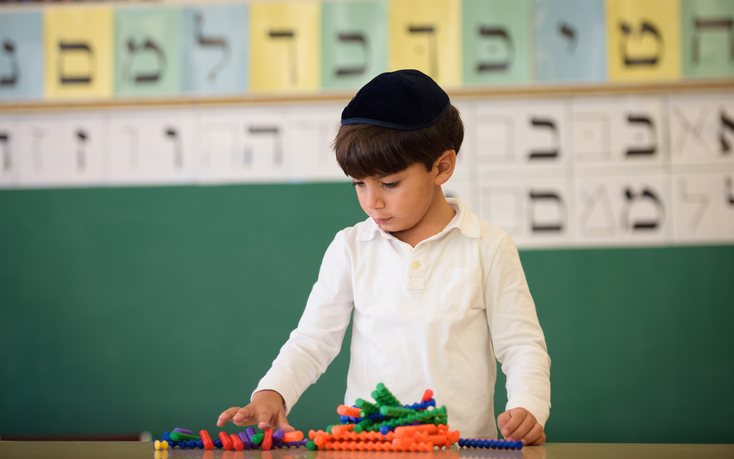 Boy from the Preschool Division playing in a classroom